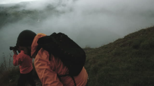 Man and woman photographers hiking in mountain of Dolomites in the fog