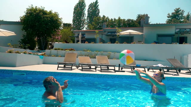 Man and Woman Playing Ball in Home Pool video