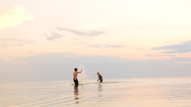 Man and woman playing in water - splash each other with water