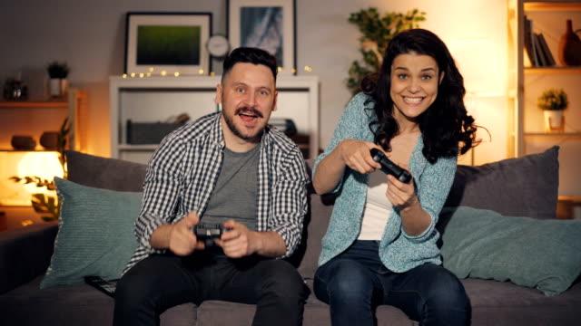 アパートでビデオゲームをしている男女、幸せな女の子が勝っている - コントロール点の映像素材/bロール