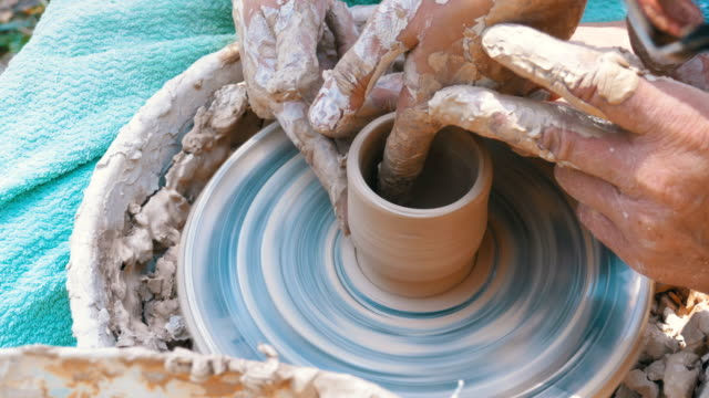Man and Woman Potter's Hands Work with Clay on a Potter's Wheel