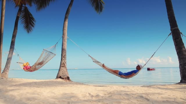 man and woman relaxing in a hammock on tropical island beach - amaca video stock e b–roll