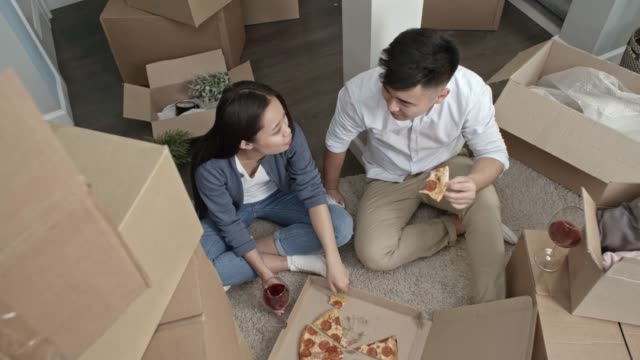 Man and Woman Relaxing with Wine and Pizza after Moving House video