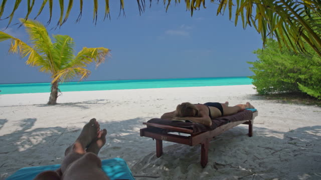 ms man and woman relaxing,napping on lounge chairs on idyllic,tropical ocean beach,maldives - penombra video stock e b–roll