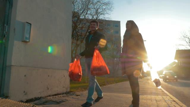 man och kvinna som återvänder hem efter shopping - walking home sunset street bildbanksvideor och videomaterial från bakom kulisserna