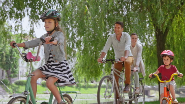 SLO MO TS Man and woman riding on a tandem bike and their two kids riding their bikes alongside them in the park