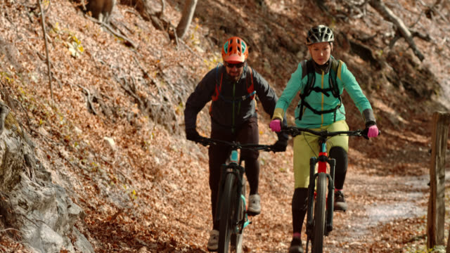 man and woman riding their mountain bikes up a sunny forest trail in fall - percorso per bicicletta video stock e b–roll
