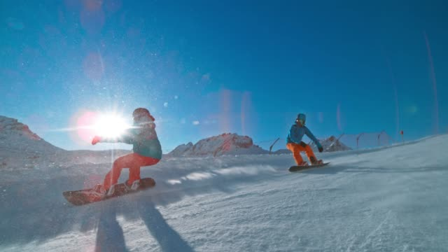 slo mo ts man and woman riding their snowboards down a sunny mountain piste - termine sportivo video stock e b–roll