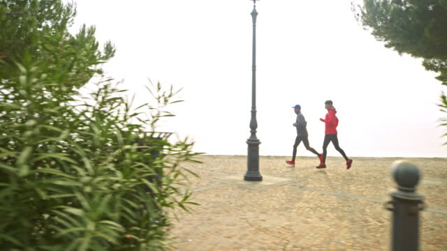 SLO MO Man and woman running along the sea on a wide pathway