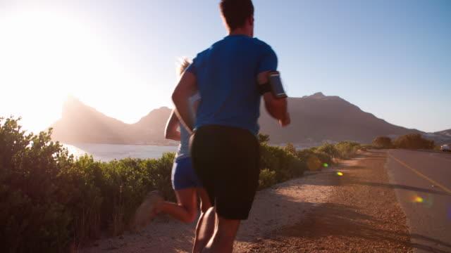 Un homme et une femme en train de courir sur route vide, ralenti, vue de derrière - Vidéo