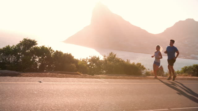 Man and woman running together on an empty coastal road video