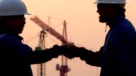 istock Man and woman shaking hands with construction site in background 1205216953