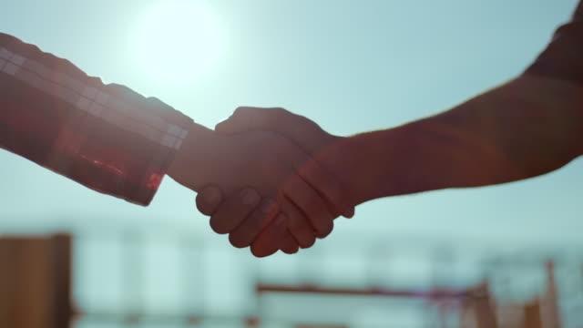 Homme et femme, serrant la main de chantier en arrière-plan - Vidéo