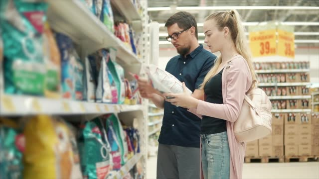 Man and woman shopping for pet food. - vídeo