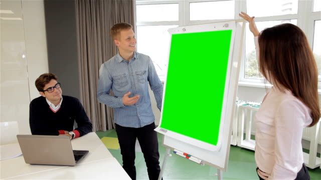 Man and woman show something on flipchart video