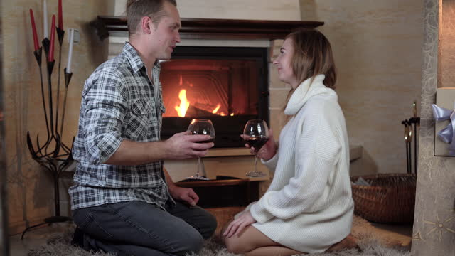 mężczyzna i kobieta siedzą na kolanach obok siebie w pobliżu kominka z ogniem. walić kieliszki i pić wino. walentynkowa koncepcja obchodów. - para aranżacja filmów i materiałów b-roll