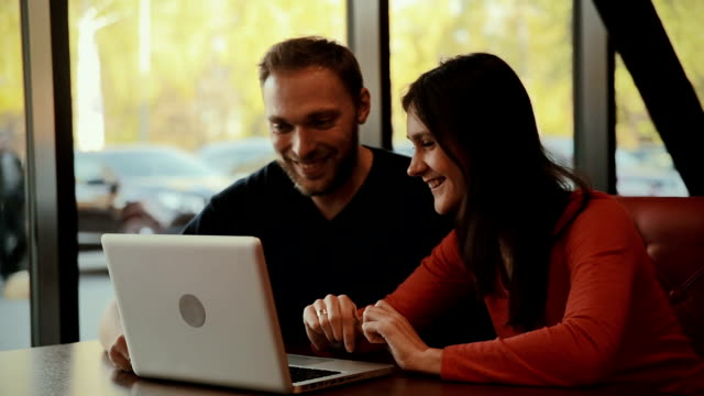man and  woman sitting at  cafe with a laptop video