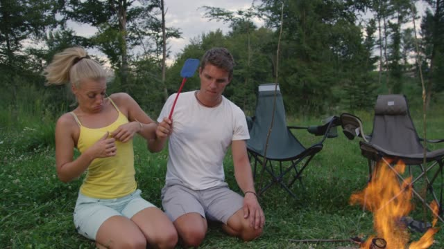 CLOSE UP: Man and woman sitting by campfire waving a fly swatter to repel bugs.