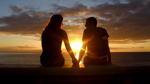 Man and woman sitting by the sea enjoy  sunset at Meloneras beach walk, Gran Canaria Couple silhouette staring at colorful twilight start kissing. Valentines Day, honeymoon romantic date concepts romance stock videos & royalty-free footage