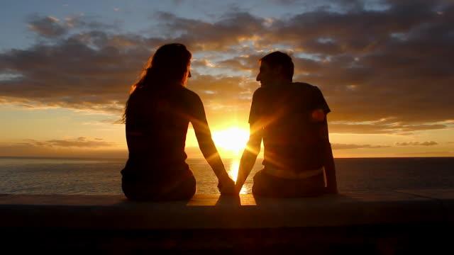 坐在海邊的一男一女在大加那利島的梅洛內拉斯海灘散步時欣賞日落 - 浪漫 個影片檔及 b 捲影像