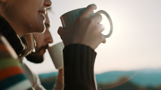 Man and woman sitting in front of the tent and drinking coffee on camping trip on the mountain video