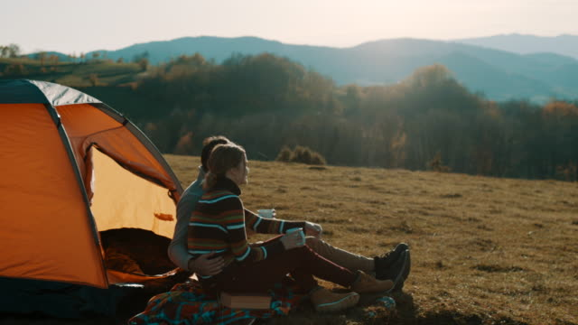man and woman sitting in front of the tent and drinking coffee on camping trip on the mountain - турист с рюкзаком стоковые видео и кадры b-roll