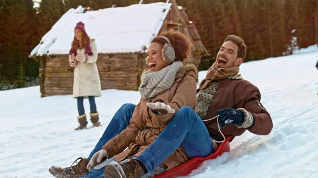 vídeos de stock e filmes b-roll de slo mo man and woman sitting on a sledge sliding down the hill after being pushed by a male friend - roupa quente