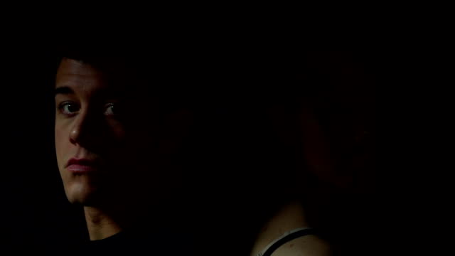 Man and woman sitting with backs together in color video