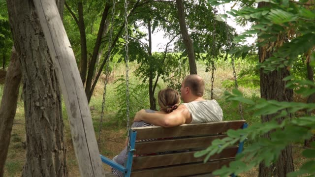 Man and woman swaying in the a bench among the trees video
