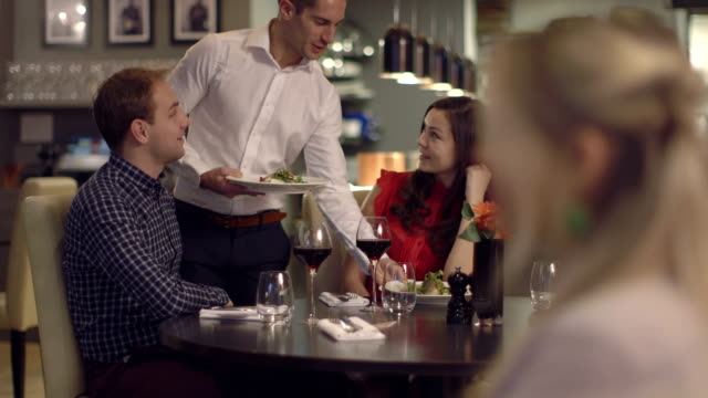 MS Man and woman talking in restaurant, waiter serving food video