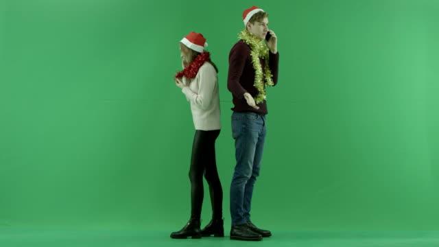 携帯電話に戻る男と女話の背景にクロマキー - サンタの帽子点の映像素材/bロール