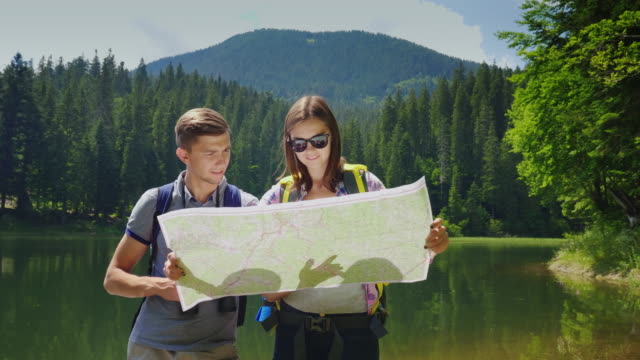 Man and woman travelers. Together they orient themselves on the map, the man looks through binoculars. Against mountains covered with forest and lake video