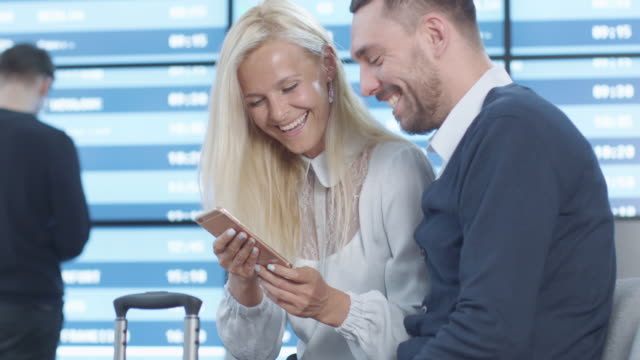 Man and Woman using Phone Together while Waiting Boarding at Departure Lounge at the Airport. video