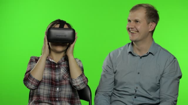 Man and woman using VR headset helmet to play game. Watching virtual reality 3D video. Chroma key