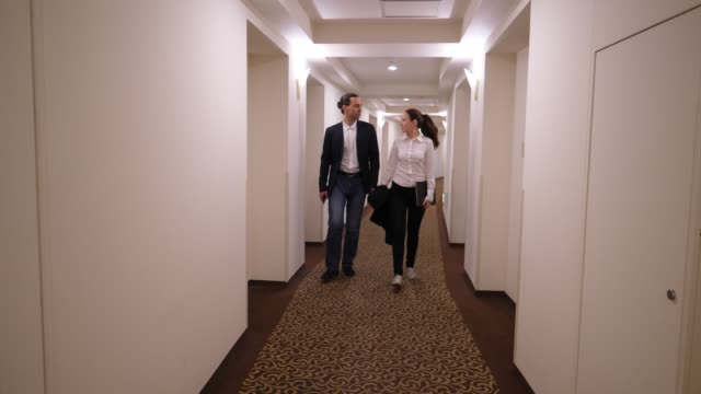 見面后,男女走過酒店走廊,時髦的休閑裝風格 - {{asset.href}} 個影片檔及 b 捲影像