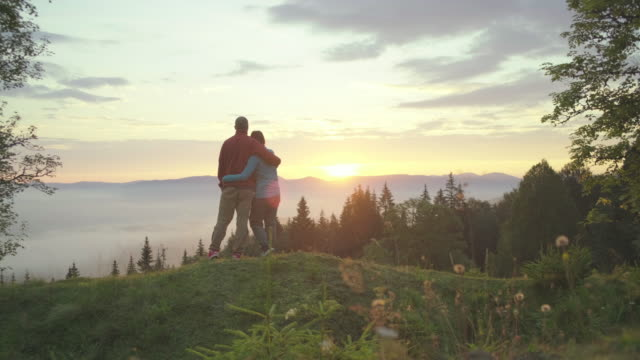 Man and woman walk on the hill and greet the sunrise in mountains. Happy couple enjoys beautiful scenery early in the morning.