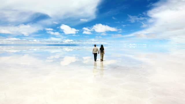 mężczyzna i kobieta spaceru w jeziorze salar de uyuni - wschodnio europejski filmów i materiałów b-roll