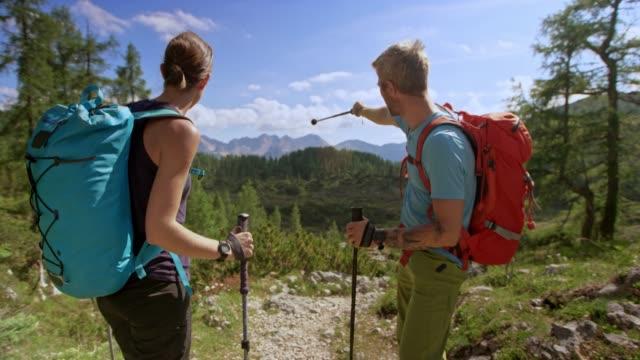 Hombre y la mujer caminando por un sendero de montaña y discutir el camino estando en el sol - vídeo