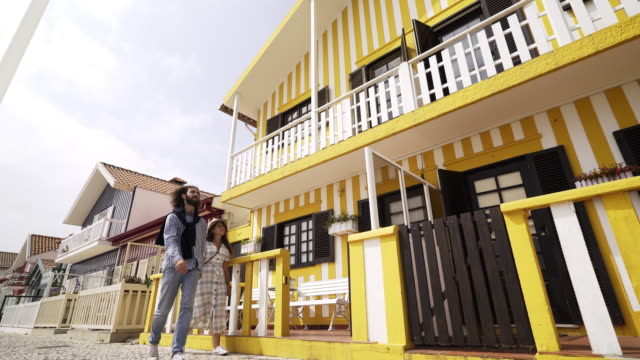 vídeos de stock e filmes b-roll de man and woman walking on street of costa nova - aveiro