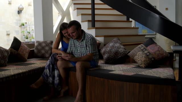 Hombre y mujer, ver video divertido sobre smartphone sentado en el sofá en casa - vídeo