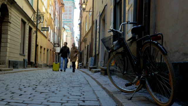 Man and woman with travel bag wandering in old city street video