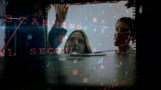 Man and woman working in computer server room while a glowing circuit board moves in foreground Animation of a Caucasian woman and man working in computer server room seen close up from inside the server rack, while glowing digital text about computer security flashes and moves in the foreground mainframe stock videos & royalty-free footage