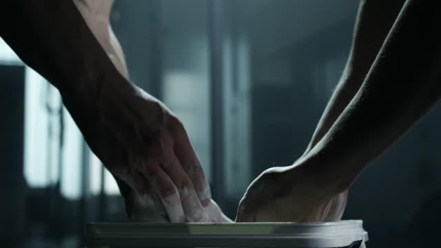 mann und frau kreidung hände vor gewichtheben in turnhalle - eimer stock-videos und b-roll-filmmaterial