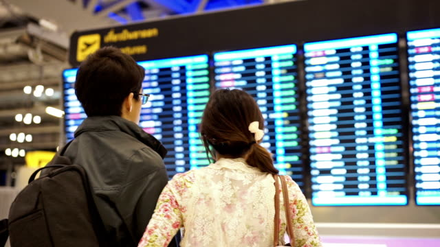 Man and Women looking at airline flight departure board video