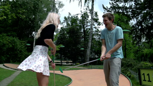 stockvideo's en b-roll-footage met man and women sword fighting with golf clubs slow motion - mini amusementpark