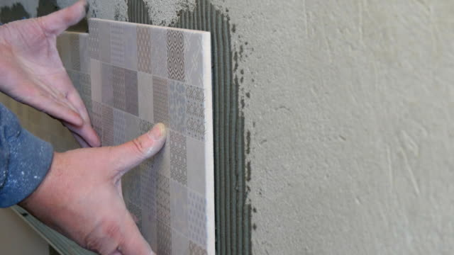 Man Applying Ceramic Tile To A Kitchen Wall video