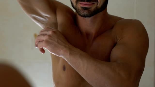 Man applying deodorant on armpit in bathroom, skin care and everyday hygiene