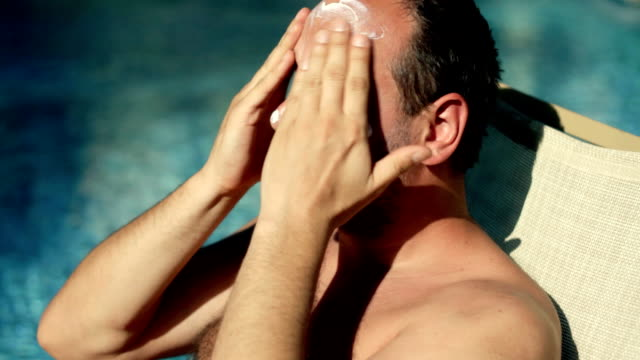 man applying protection lotion on his face - sun cream stock videos & royalty-free footage