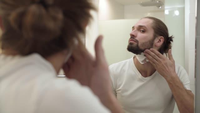 man applicera raklödder på ansiktsvård och tittar i spegeln - skägg bildbanksvideor och videomaterial från bakom kulisserna