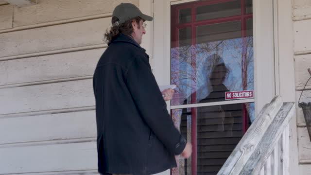 stockvideo's en b-roll-footage met man naderen van een deur en begint kloppen houden van een notebook - verlaten slechte staat